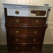 A chest of drawers with the top drawer painted partly white.