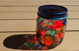 A recycled glass jar that has been decorated to resemble stained glass.