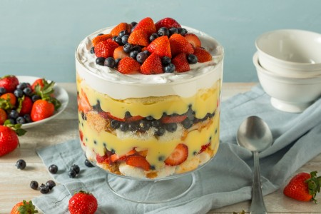 A trifle dessert with whipped cream, fruit and angel food cake.