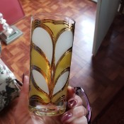A decorative drinking glass in yellow and white with gold trim.