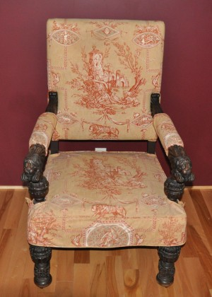 An armchair with ornate fabric.