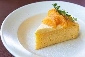 A slice of orange cake on a plate.