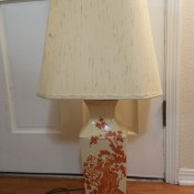 A cream colored lamp with red decorations.