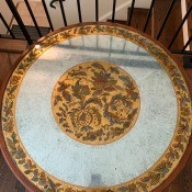 A round coffee table with an ornate top.