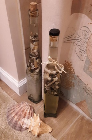 A decorative bottle filled with sand and shells.