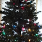 A Christmas tree with some of the lights out.
