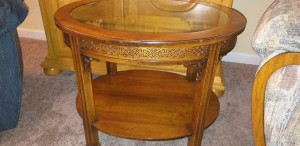 A round Brandt end table with a glass top.
