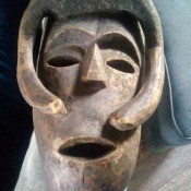A carved wooden mask in a primitive style.