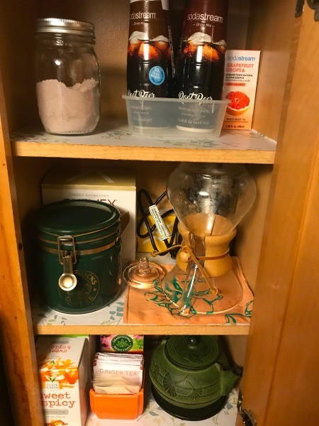 A cabinet containing teas, coffee and Soda Stream items.