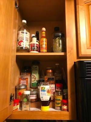 A cabinet containing spices and other cooking ingredients.