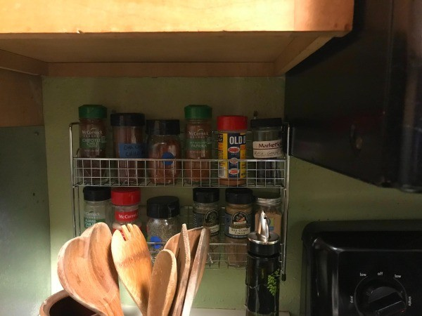 A small spice rack underneath a cabinet.