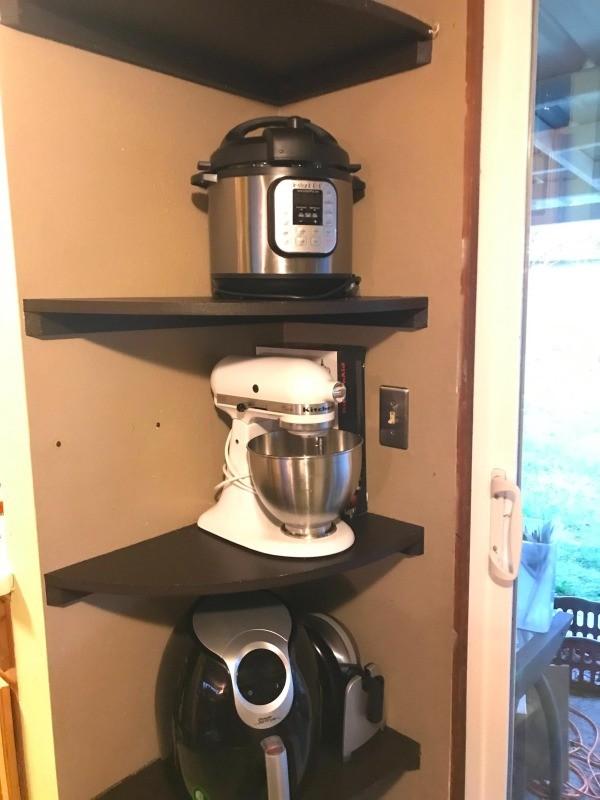 Appliances stored on a corner shelf.