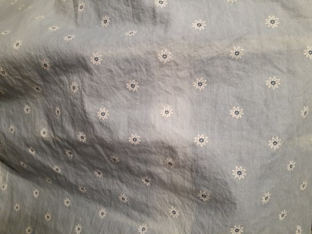 A faded line in the middle of a light colored fabric.