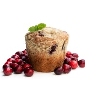 A cranberry muffin next to fresh cranberries.