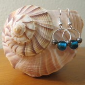 Two bead and wire earrings hanging on a seashell.