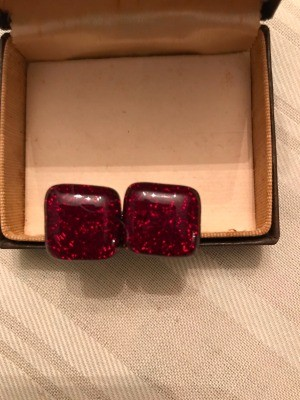 A pair of red cufflinks.