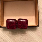 A pair of red cufflinks.