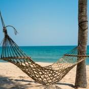 A hammock on a sandy beach.