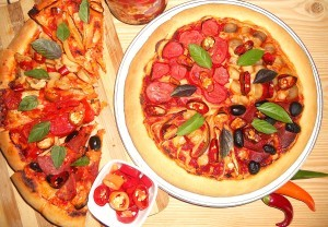 A baked pizza next to slices of pizza.