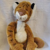 A stuffed tiger with hands and feet.