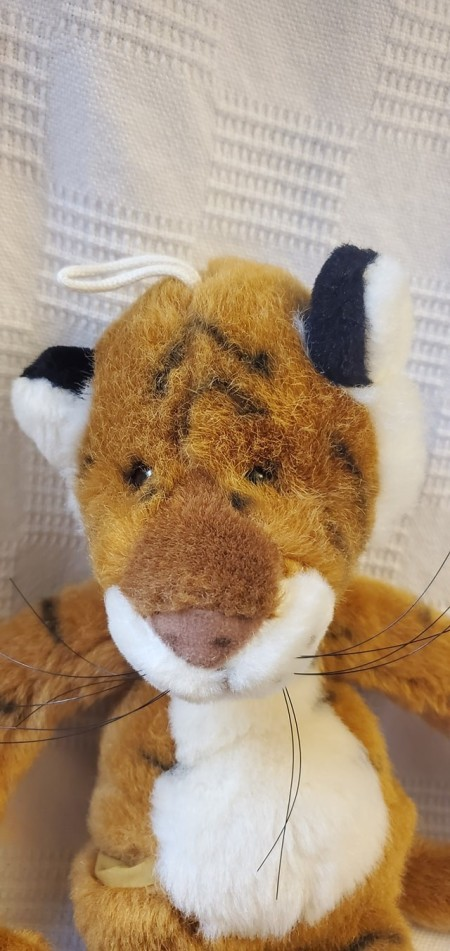 A stuffed tiger with a hanging loop on its head.