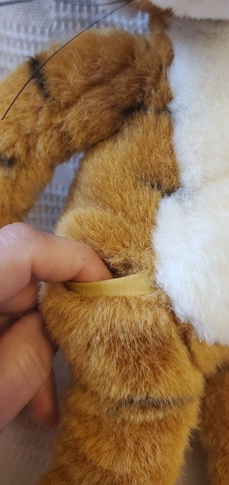 A pocket on the side of a stuffed tiger.