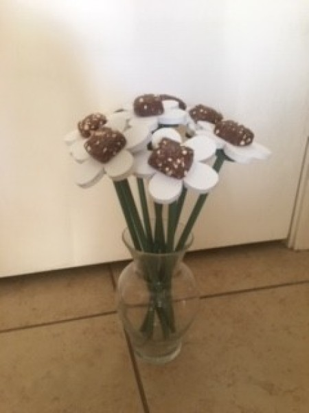 A bouquet of wooden flowers with chocolate centers.