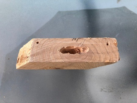 An angled piece of wood with a hole drilled in the middle.