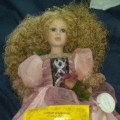 A decorative porcelain doll in a fancy pink dress.