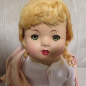 An old doll with blonde hair.