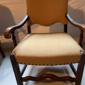 A chair with wooden arms and legs.