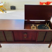 An old stereo cabinet with an open lid.