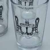 Small juice glasses with a drawing of a table with two chairs.