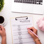 A wedding budget list on a clipboard.