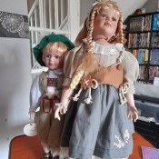 Two porcelain dolls in old fashioned outfits.