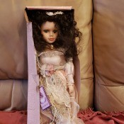 A porcelain doll in a box.