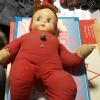 Baby doll with stuffed body in a red outfit.