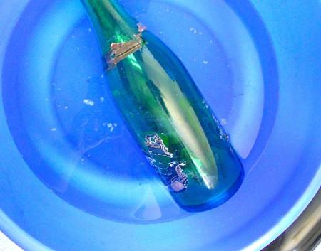 Glass bottle in a bath of warm water.
