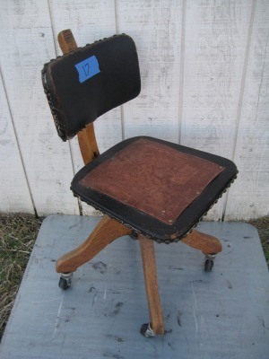 A wooden office chair with a leather seat.