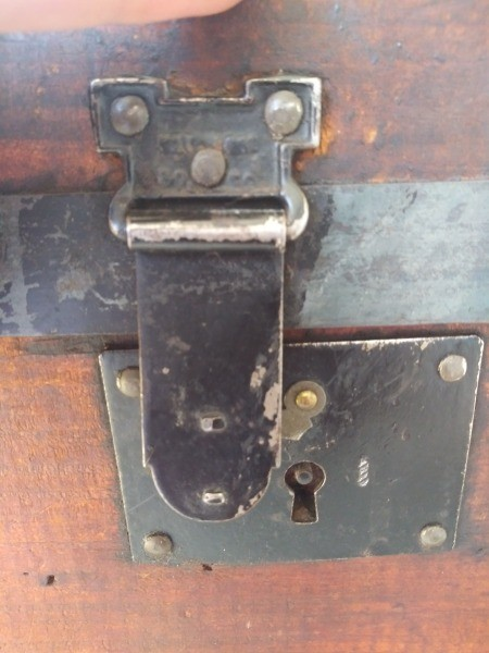 The latch on an old wooden trunk.