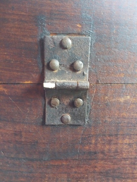 A hinge on an old trunk.