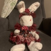 A stuffed bunny wearing a fancy headband and dress.