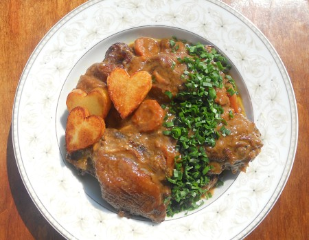 A plate of coq a vin with fried potatoes.