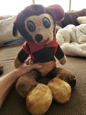 A vintage stuffed animal wearing red.