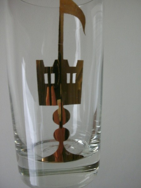 A drinking glass with a gold emblem.