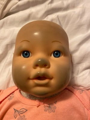 A doll with discolored places on the nose and cheeks.