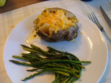 A loaded baked potato with asparagus