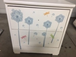 A white dresser with sticker designs on the front of the drawers.