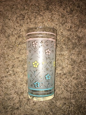 A drinking glass with a floral pattern.