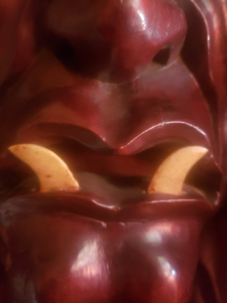 A close up of the mouth of a wooden mask.